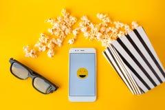 Biały smartphone z smilies na ekranie, 3d szkłach, czarny i biały pasiastym papierowym pudełku i rozrzuconym popkornie, fotografia stock