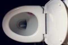 Biały toaletowy puchar w łazience z czarnym tłem Obraz Stock