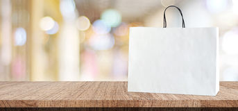 Biały torba na zakupy na drewnianym stole nad zamazanym sklepu tłem Fotografia Royalty Free