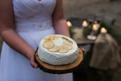 Biały tort z cytrynami w ręce panna młoda Tort na drewnianej tacy Obrazy Stock