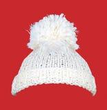 Biały trykotowy wełna kapelusz na czerwieni Obrazy Stock