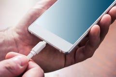 Biały USB kabel Łączący Z Białym telefonem komórkowym, Holded Męskimi rękami Obrazy Royalty Free