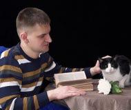 Biały waleczny mężczyzna obok stołu, kłama książkę i róża kwiatu dokąd kot siedzi zdjęcie stock