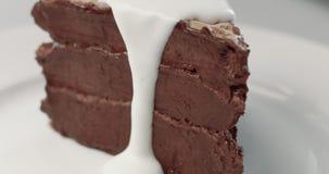 Biały waniliowy kremowy dolewanie na kawałku czekoladowy tort zbiory