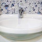 Biały washbasin fajans i chrom instalaci wodnokanalizacyjnej faucet w bathro zdjęcia royalty free