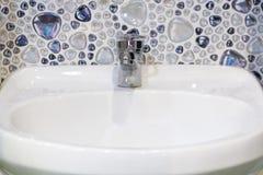 Biały washbasin fajans i chrom instalaci wodnokanalizacyjnej faucet w bathro obraz royalty free