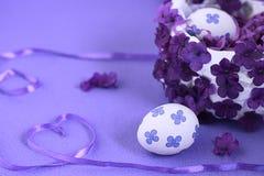 Biały Wielkanocny kosz z jajkami, dekorującymi z kwiatami na tle z faborkiem w formie serca Fiołkowi odcienie fotografia stock