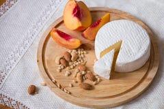 Biały wyśmienicie domowej roboty camambert ser na drewnianym talerzu słuzyć z migdałami, nerkodrzewem, sosnowymi dokrętkami i brz Fotografia Royalty Free