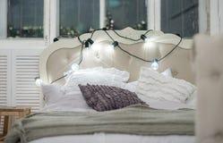 Biały wygodny łóżko z rocznik poduszką i bożonarodzeniowe światła, defocus zdjęcie royalty free