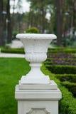 Biała architektoniczna waza na piedestale w parku Zdjęcie Stock