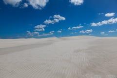 Białe chmury przeciw niebieskiemu niebu i piasek Zdjęcia Royalty Free