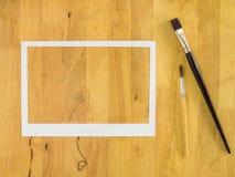 Białego papieru rama na drewnianym tle Zdjęcia Stock