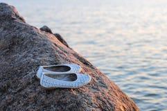 Biała kobieta buty na rockowym pobliskim morzu Obraz Royalty Free