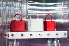Biała torba i dwa kobiety ` s toreb czerwony stojak na stole Zdjęcie Royalty Free