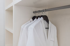 Biały bathrobe z drewnianymi wieszakami w garderobie Zdjęcie Royalty Free