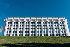 Biały budynek Przeciw niebieskiemu niebu Zielona trawa w przedpolu Obraz Royalty Free