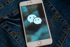 Bia?y iPhone z logo og?lnospo?eczny medialny WeChat od Chiny na ekranie Og?lnospo?eczna medialna ikona zdjęcie stock