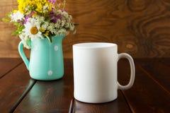Biały kawowego kubka nieociosany mockup z wildflowers w mennicy zieleni va Fotografia Stock