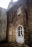 Bia?y p??cyrk?owy drzwi z szk?em w kamiennej ?cianie stary miasteczko w Budva, Montenegro fotografia stock