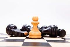 Biały pionek i czarne postacie, szachowa gra Fotografia Stock