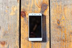 Biały smartphone lying on the beach na drewnianym stole obrazy stock