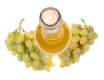 Biały wino w butelce i winogronach Zdjęcia Royalty Free