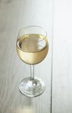 Biały wino w szkle na rocznika tle Zdjęcia Stock