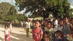 BIABAS, BOHOL, FILIPPINE - 5 DICEMBRE 2015: Gli studenti dei bambini interagiscono con i turisti maschii video d archivio