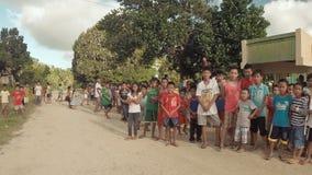 BIABAS, BOHOL, FILIPPINE - 5 DICEMBRE 2015: Il turista lancia il fuco per gli scolari e comunica con loro archivi video