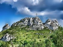 Biaklo - inlier hill located on Cracow - Czestochowa upland in Poland. Little Giewont inlier hill with metal cross located in the Sokole Mountains reserve in stock photos
