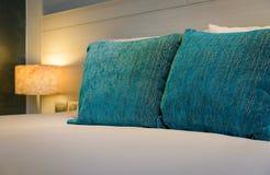 Biali łóżkowi prześcieradła z lekkim lampowym dekoracji wnętrzem sypialnia - sztaplowanie poduszki na łóżku fotografia stock