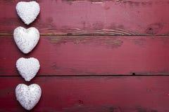 Biali błyskotliwość serca na czerwonym drewnianym tle Obrazy Royalty Free