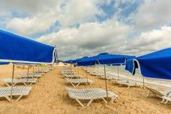 Biali bryczka hole i błękitny parasola stojak na plaży w th Fotografia Royalty Free
