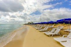 Biali bryczka hole i błękitny parasola stojak na plaży w th Zdjęcia Royalty Free