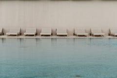 Biali deckchairs obok pływackiego basenu z krystaliczną błękitne wody i loungers Obrazy Royalty Free