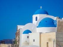 Biali domy, kościół i błękitne kopuły w Oia wiosce, zdjęcia stock