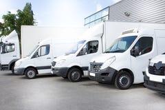 Biali doręczeniowi samochody dostawczy przewożą samochodem na parking w przodzie na wejściu magazyn przy dystrybucja samochodem d zdjęcia royalty free