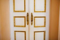 Biali drzwi z złocistymi podstrzyżenia i złota rękojeściami zdjęcie stock