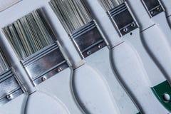 Biali farb muśnięcia i puszka nafciana farba na białym drewnianym stole Zdjęcia Stock