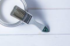 Biali farb muśnięcia i puszka nafciana farba na białym drewnianym stole Obrazy Stock
