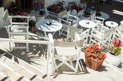 Biali Greccy schodki z stołami i krzesłami typowa grecka ulica Zdjęcie Royalty Free