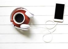 Biali hełmofony i kawowa czerwona filiżanka z mądrze telefonem na białym drewnianym biurko stole Muzyki i stylu życia pojęcie zdjęcia stock