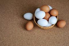 Biali i brown jajka w słomianym koszu Fotografia Royalty Free