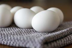 Biali jajka na popielatym i białym w kratkę kuchennym ręczniku na drewnianego stół obrazy royalty free
