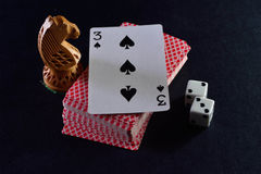 Biali kostka do gry dobierać do pary, karty i szachów rycerze na czarnym tle Fotografia Stock