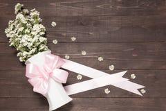 Biali krajaczy kwiaty są w wazie z faborkiem na drewnianym b Zdjęcia Stock