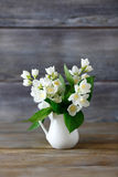 Biali kwiaty w wazie na drewnianej powierzchni obrazy royalty free