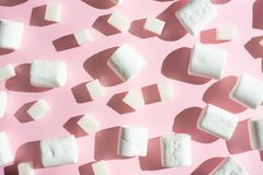 Biali marshmallows z cukrowymi sześcianami na różowym tle z ciężkimi cieniami, Zdolność używać jako tło pojęcie fotografia stock