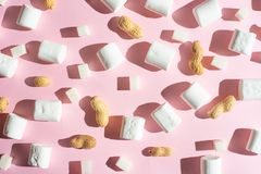 Biali marshmallows z kawałkami cukier i dokrętki na różowym tle z ciężkimi cieniami, Zdolność używać jako tło, zdjęcie royalty free