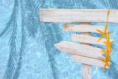 Biali nieociosani drewniani strzałkowaci znaki z błękitną żółtą rozgwiazdą nad turkusowego błękita mozaiki basenu wodą zdjęcia stock